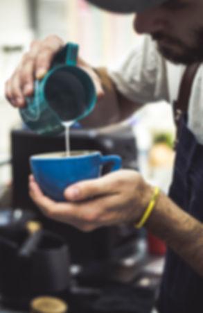 Barisa pouring a heart latte art pattern in cappuccino in Bloom Coffee Belgrade.