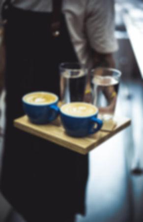 Barista servng two cappuccinos in Bloom Coffe Begrade.