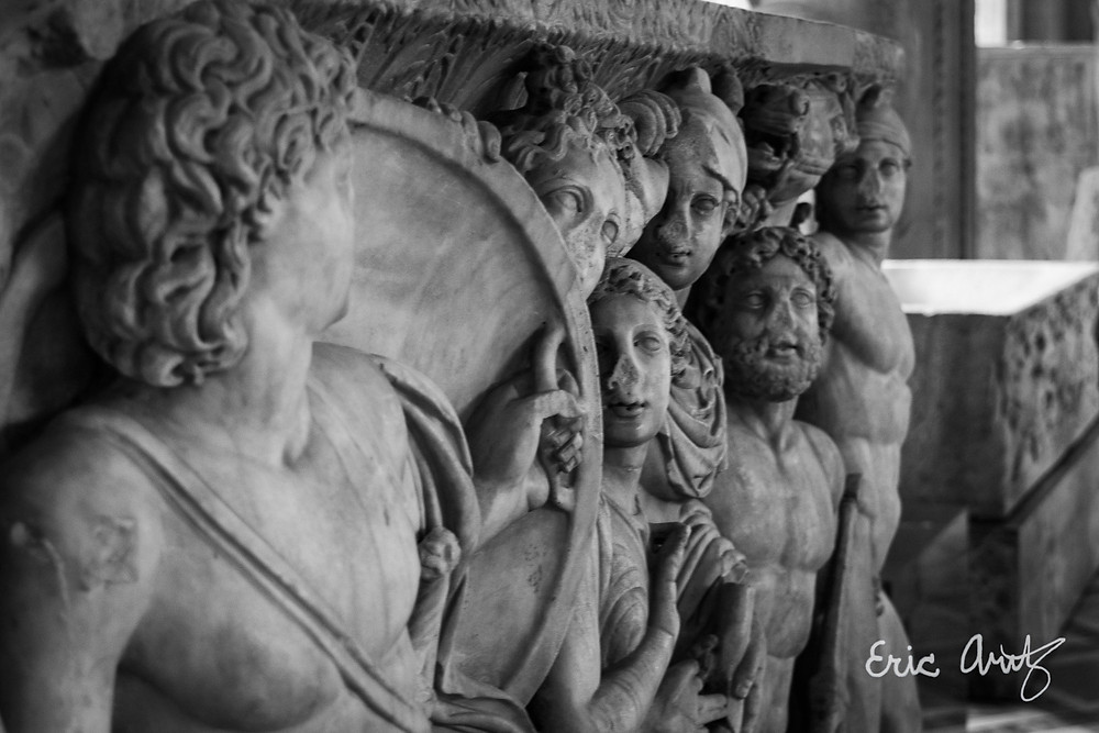 A black and white photo of a collection of figures adorning an ancient Roman tomb at the Louvre in Paris