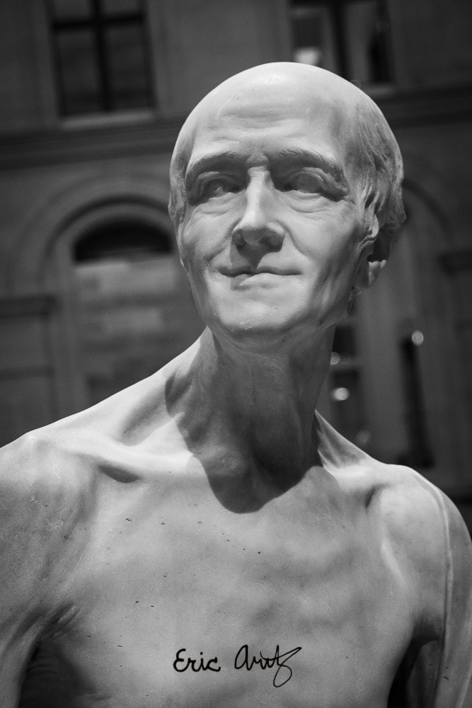 A statue of an elderly man at the Louvre in Paris