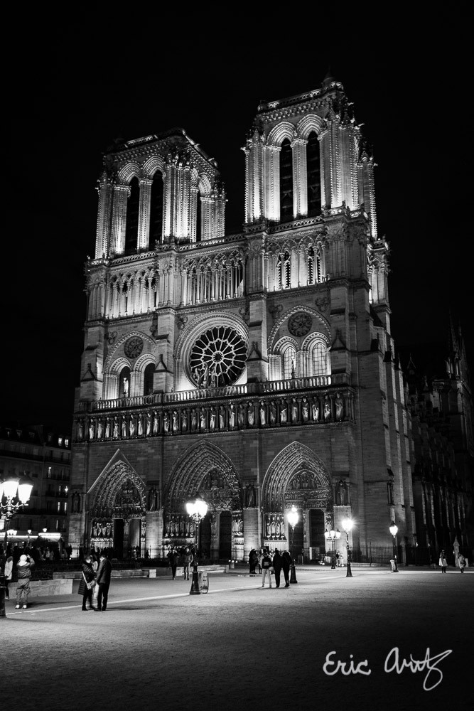 A black and white photo of Notre-Dame de Paris lit up at night