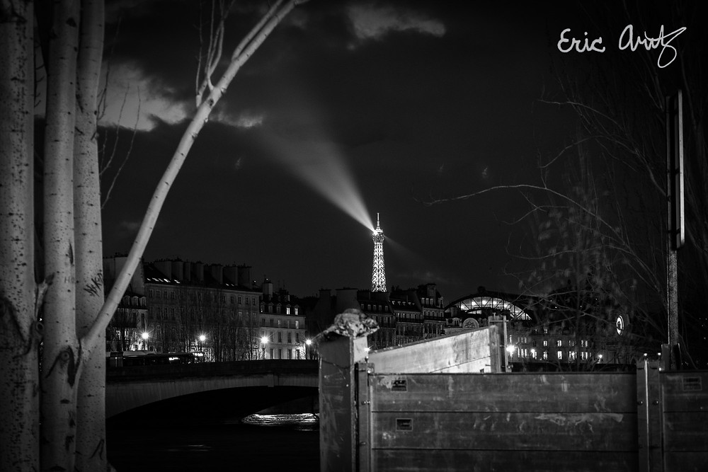 A black and white photo of the Eiffel Tower's rotating spotlight frozen in time in Paris