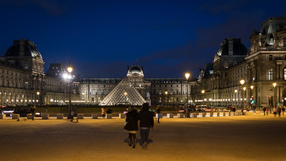 Widescreen shot of the Louvre Museum at night in Paris
