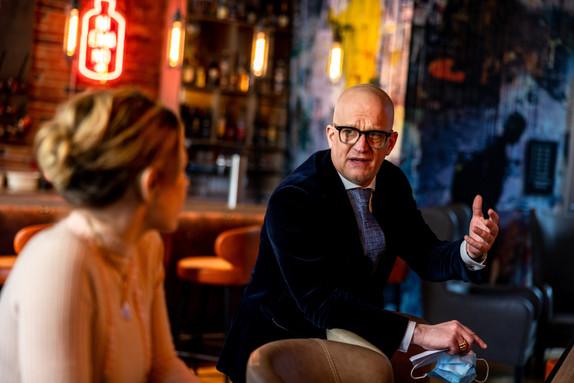 Bräutigam unterhält sich angeregt mit Gast in der Bar
