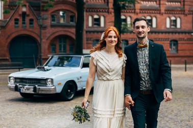 Brautpaar im Vintage Look posiert vor blauem Oldtimer