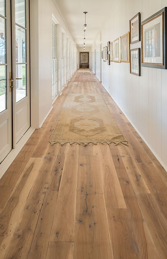 long hallway with wood flooring, doors, and artwork