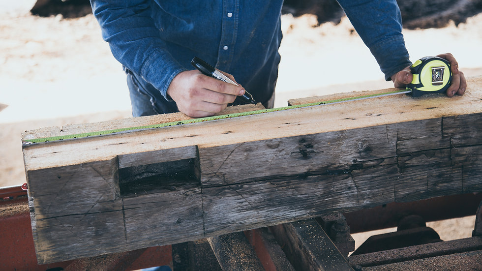man measuring hardwood wide plank