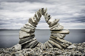 A sculpture of stones forming an arch overlooking the ocean.