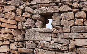 A small opening in a wall made of stones.