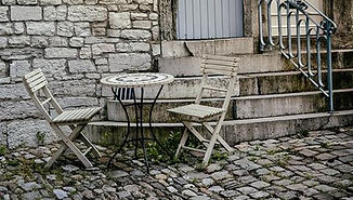 Small table and two chairs on cobblestoness in front of a stone house.