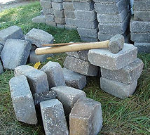 Piles of stones and a slege hammer to build a wall.