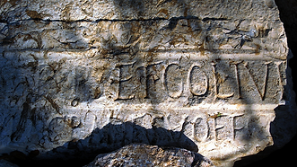 Ancient stone fragment with Latin engraving.