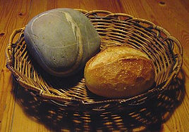 A basket with a loaf of bread and a large stone.