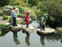 Children using stepping stones to cross a small stream in a park.