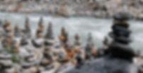 Prayer stone stacks on the stone strewn bank of a stream.