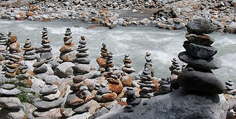 Prayer stone stacks on the stone strewn bank of a stream.