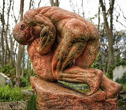 A stone statute of Sisyphus rolling the boulder.
