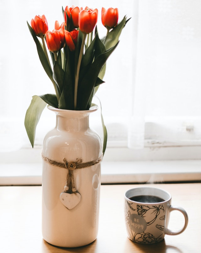 Red tulips in a white vase with a cup of coffee