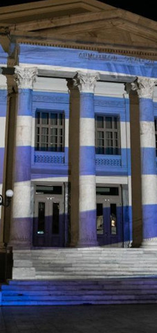 The Municipal Theatre of Piraeus illuminated with Greek flag 3D projection.