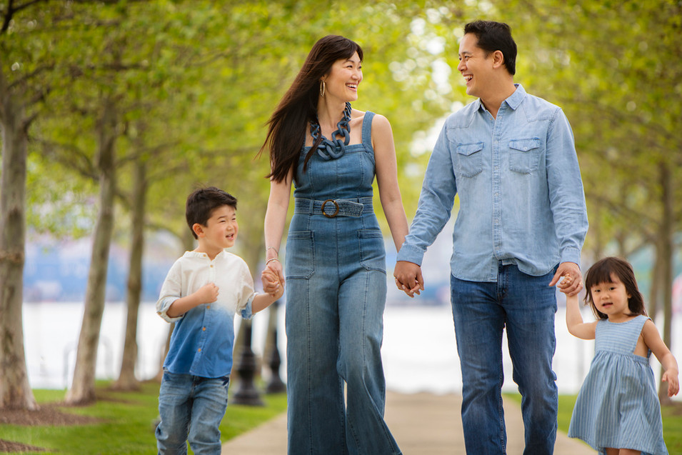 Professional outdoor family portrait of a young family walking in a park