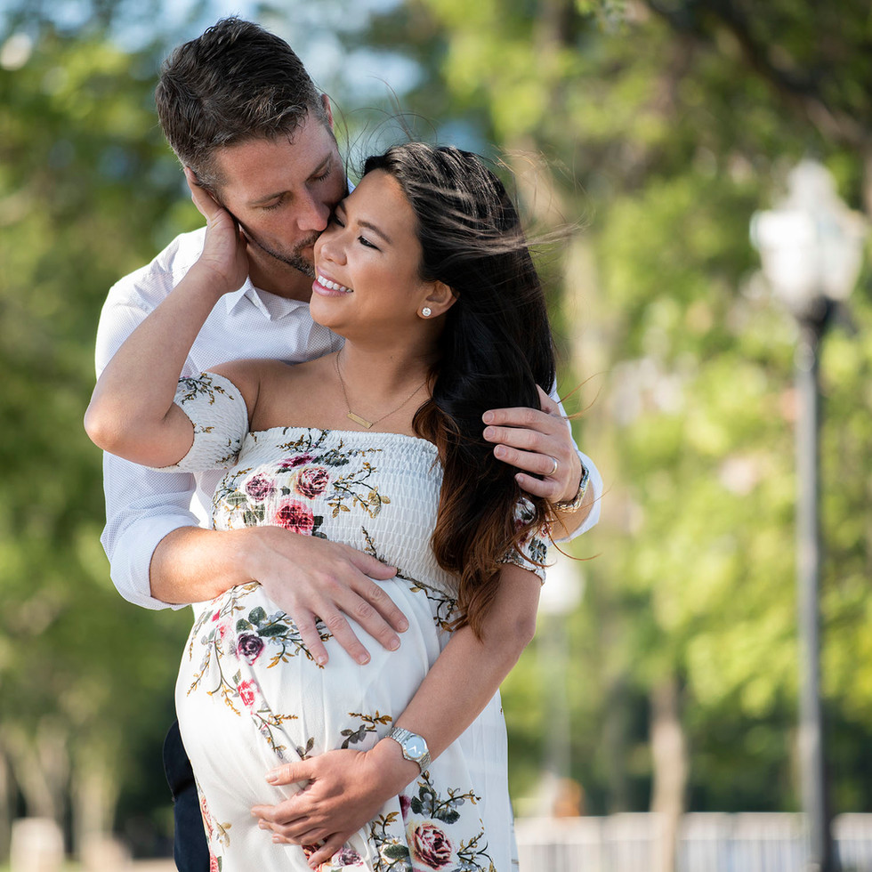 Professional outdoor maternity portrait of husband hugging and kissing wife