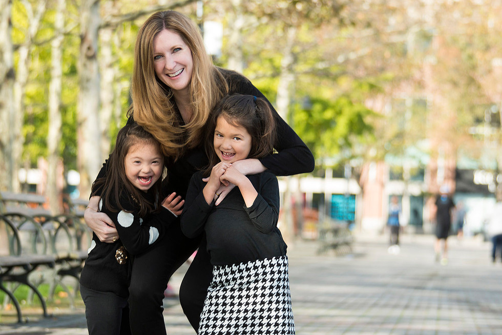 Professional outdoor family portrait of mother playing with daughters