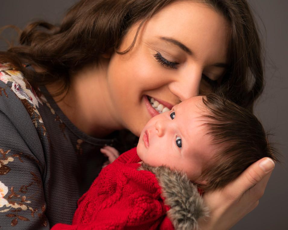 Professional studio family portrait of a mother kissing newborn