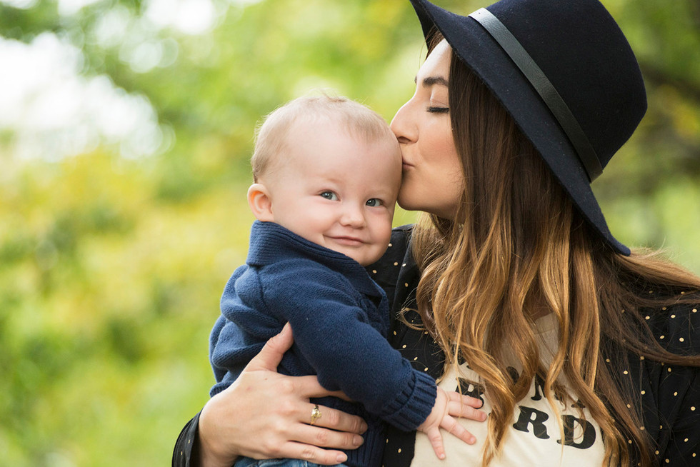 Professional outdoor family portrait of a young mother kissing baby