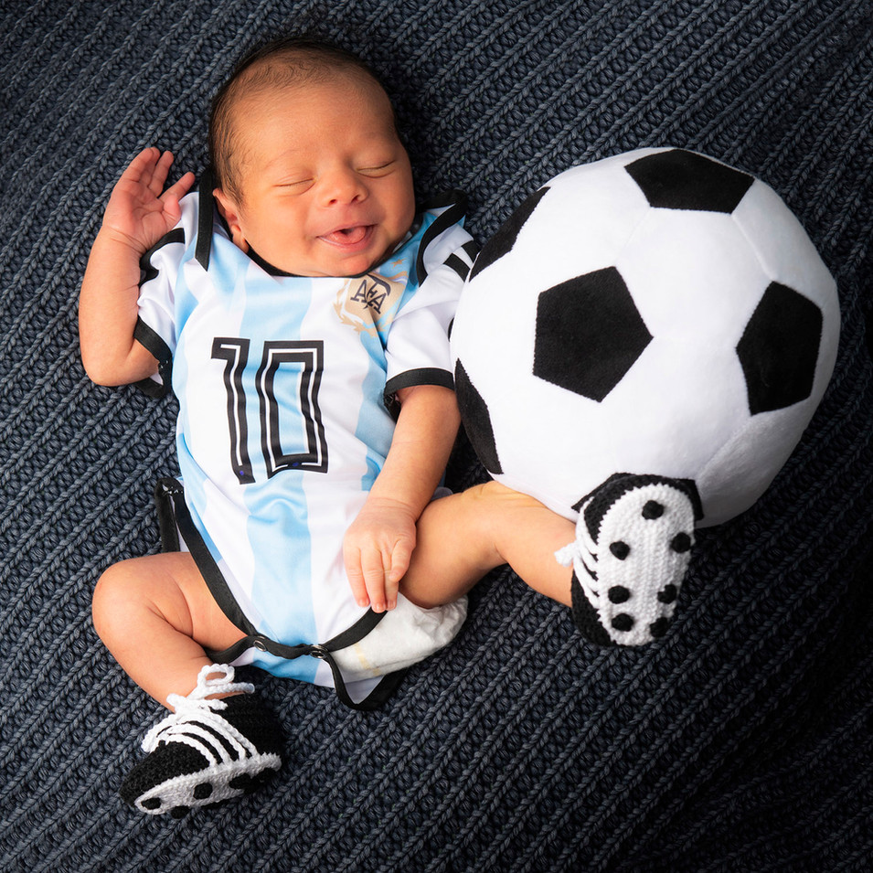 Professional portrait of a newborn boy and a soccer ball