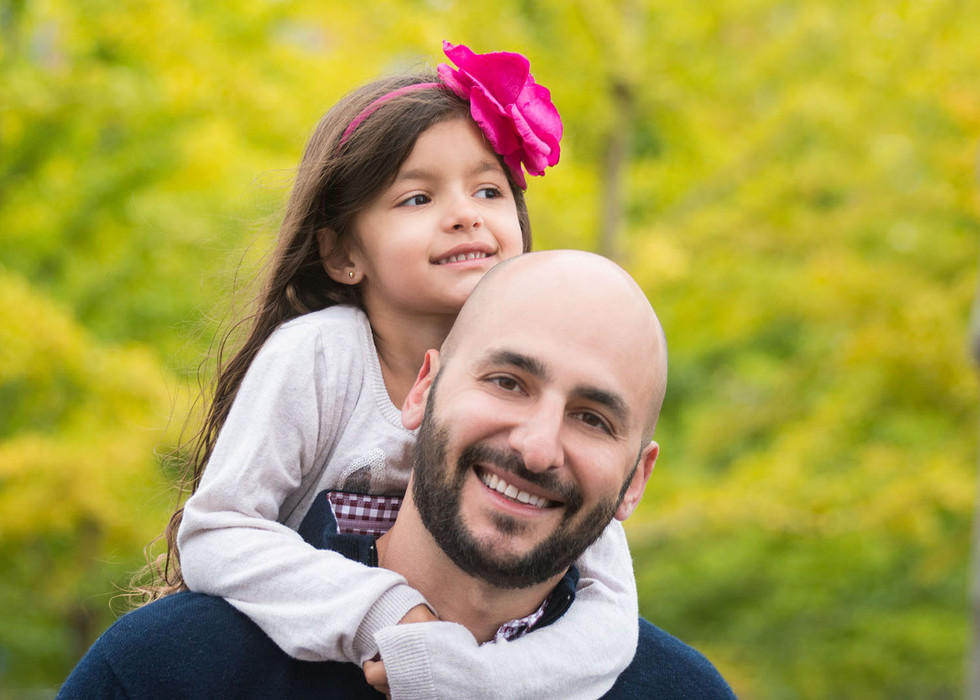 Professional outdoor family portrait of a little girl hugging her father
