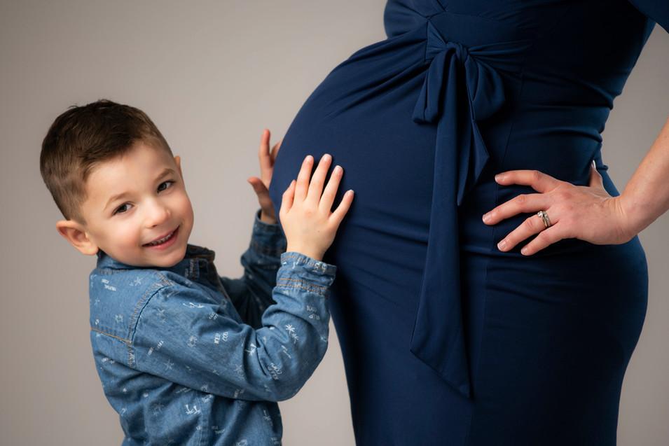 Professional studio maternity portrait of little boy hugging pregnant mother