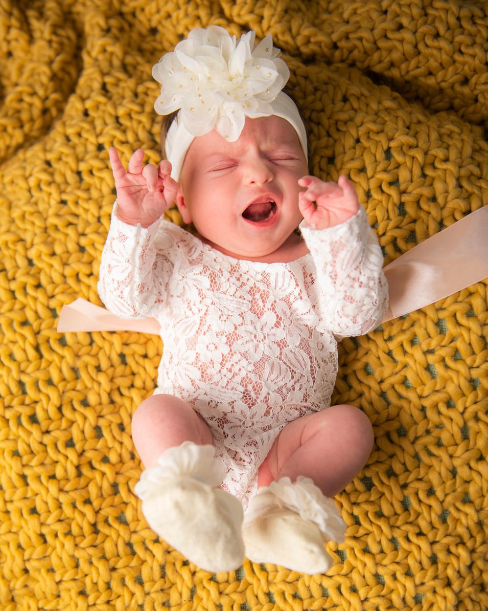 Professional portrait of a newborn girl crying