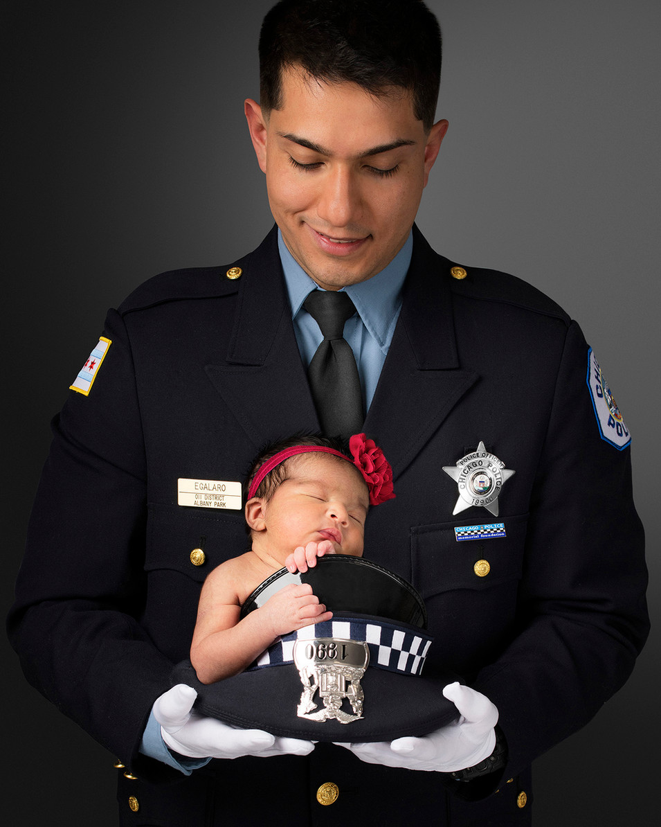 Professional Portrait of police officer holding newborn baby daughter