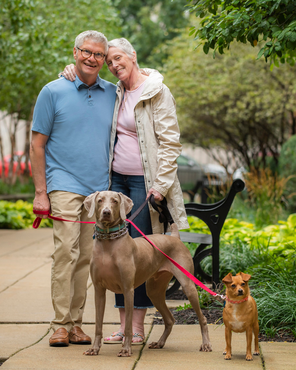 Professional outdoor family portrait of an elderly couple with dogs