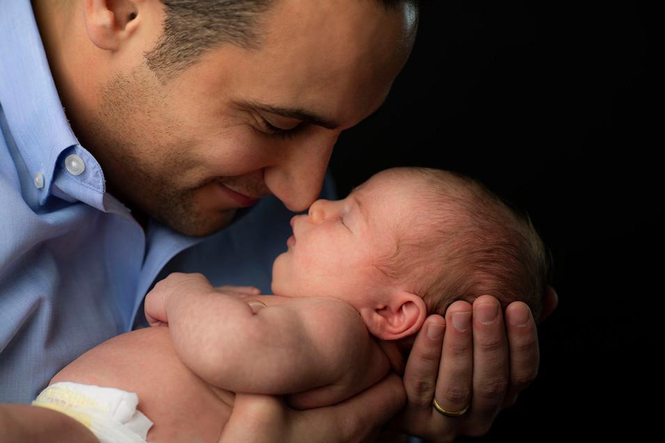 Professional studio family portrait of a father kissing newborn