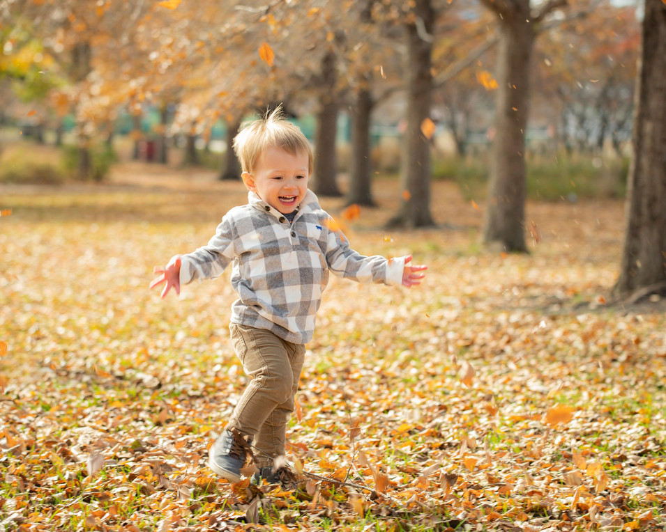 Professional outdoor portrait of a toddler running