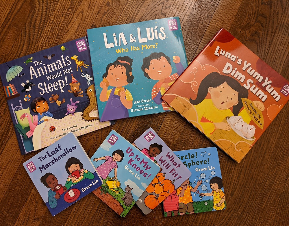 Seven books from the Storytelling Math series are shown spread across a wooden floor.