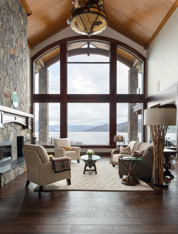 Massive solid wood frame bay window inside high ceiling chateau overlooking the mountains.