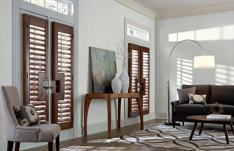 Sitting room with three large windows with wood shutters.