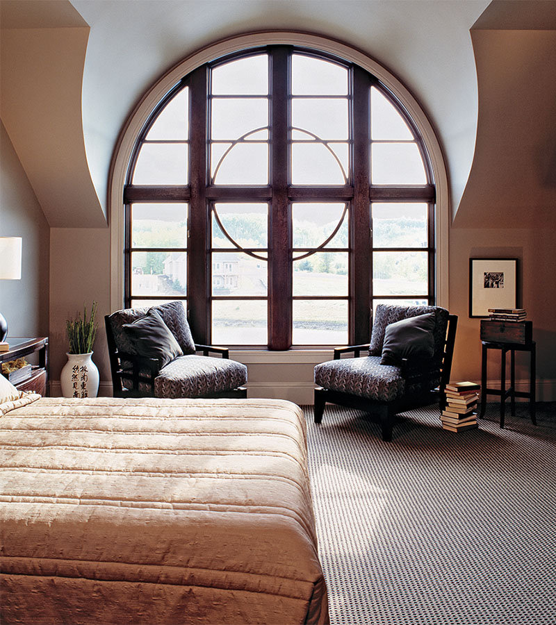 A bedroom with a large rounded wood frame window with circular feature