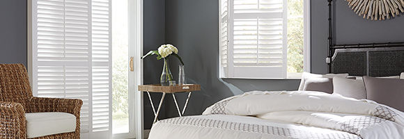 Bedroom with two large windows featuring durable and cost-effective composite shutters in white.