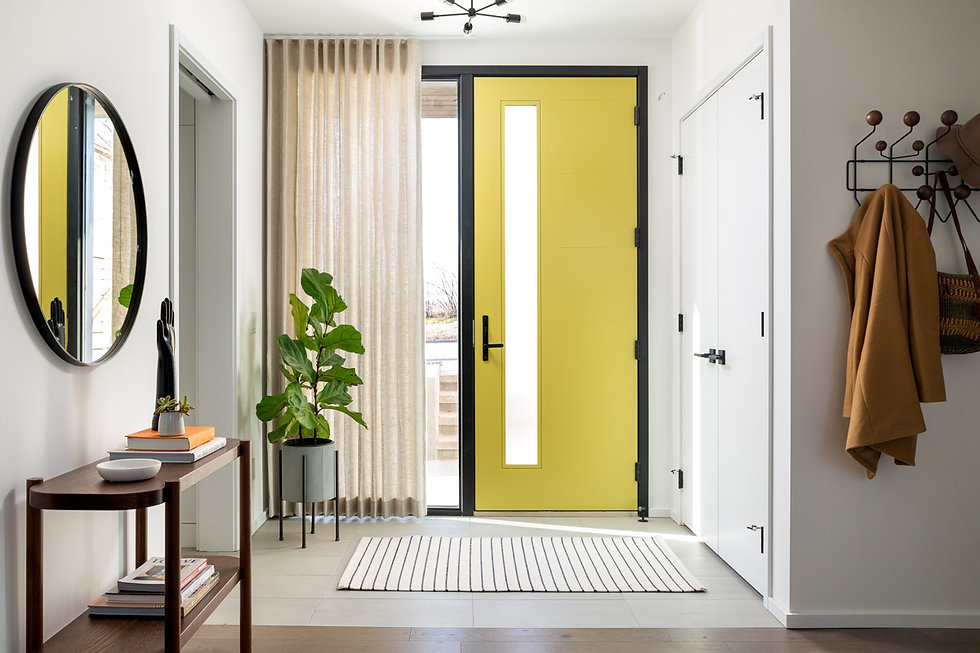 Modern front entry with bright yellow door that has a long and narrow vertical window detail, floor to ceiling window framing the left side of the door. All framed in black, with beige curtain partially covering the window. Plant on the left side of window and large white closet on the wall to the right of the door.