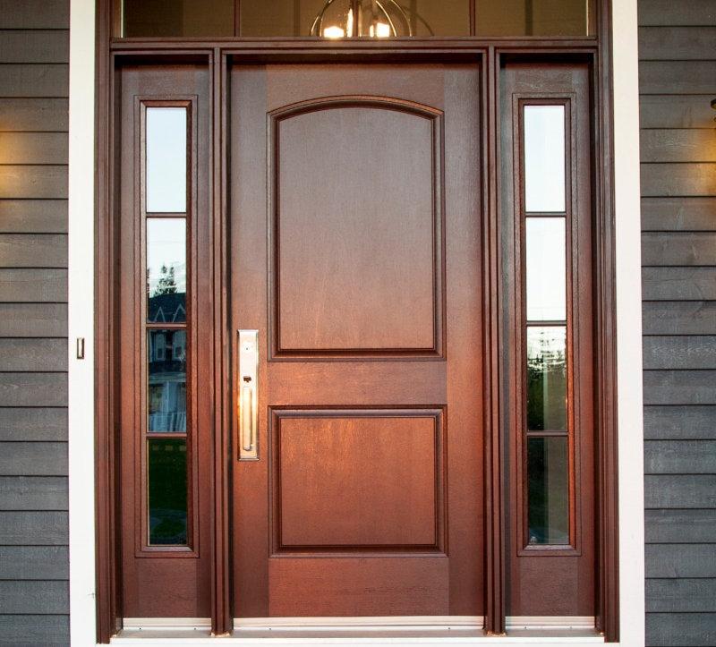Wood front door with narrow vertical windows framing both sides of the door.