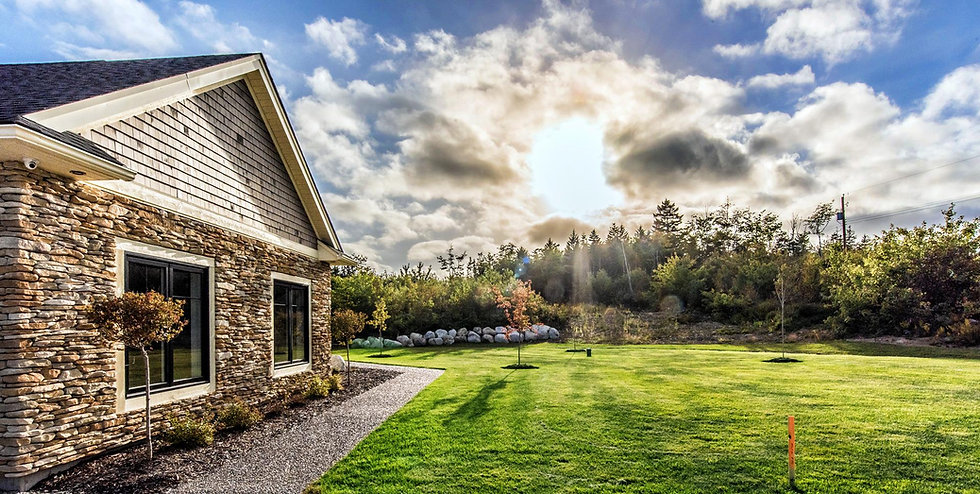 Outside a new home with stone siding and wood shakes on the vaulted wall. Large black framed window with small pruned tree in front. Cedar mulch and gravel ground cover. Large green lawn and bright blue sky with fluffy white clouds. Lots of trees in the background.