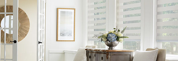Room with three windows featuring white layered shades. Table with flower arrangement.
