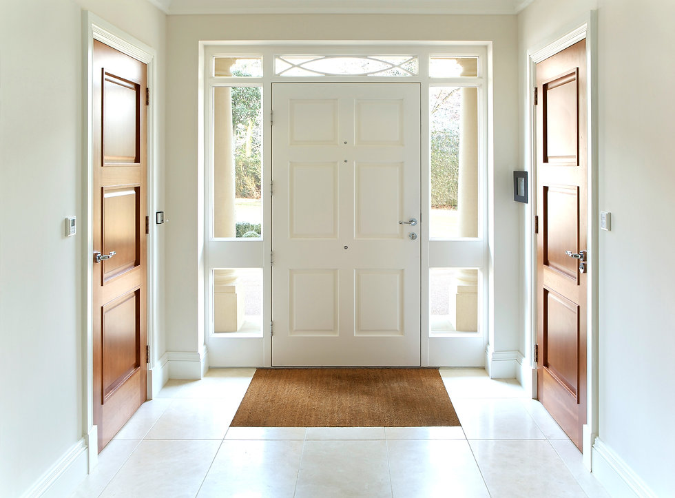 Front entry with windows framing a white door, showing trees and two large white columns outside of windows. Brown doors on the other walls on each side of the front entry.