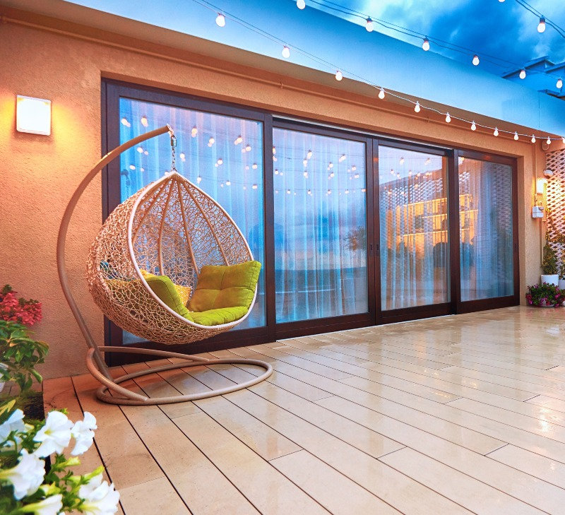 A sliding patio door on a well lit patio with patio furniture