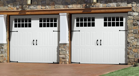 Stone house featuring white authentic looking carriage house garage doors.