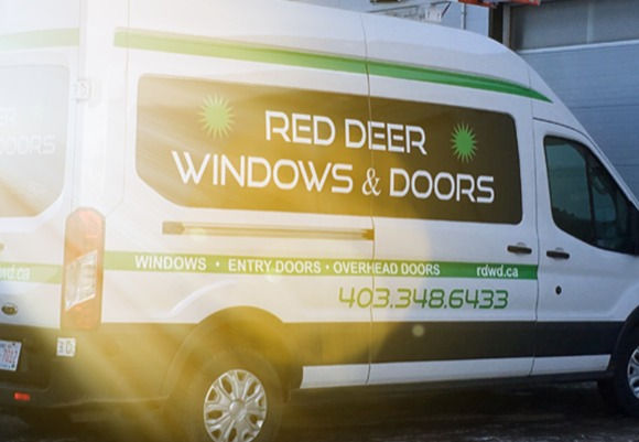 RED DEER WINDOWS & DOORS on side of white van. Two bright neon green asterisks.RDWD.
