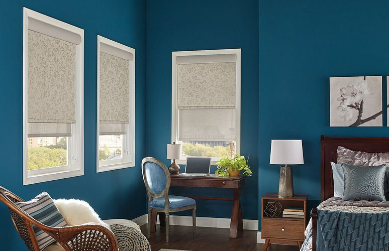 Blue bedroom with three windowing featuring pulldown cream shades.